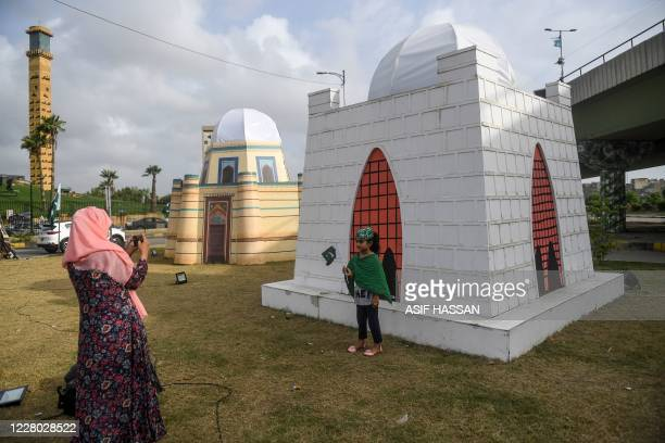 Woman takes a photograph of her daughter beside a model of the tomb of Mohammad Ali Jinnah, the founder of Pakistan, alongside a street in Karachi on...