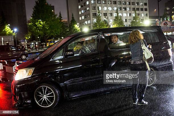 A woman takes a photograph of sumo wrestlers as they sit in traffic after competing in the Tokyo Grand Sumo tournament at the Ryogoku Kokugikan on...