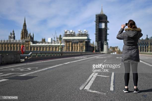 A woman takes a photograph of The Houses of Parliament from the middle of Westminster Bridge in the sunshine in central London on the morning of...