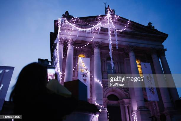 A woman takes a photograph of the lightandsound installation 'The Depth Of Darkness The Return Of The Light' by artist Anne Hardy on the facade of...
