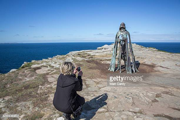 A woman takes a photograph of the new 'Gallos' sculpture that has been erected at Tintagel Castle in Tintagel on April 28 2016 in Cornwall England...