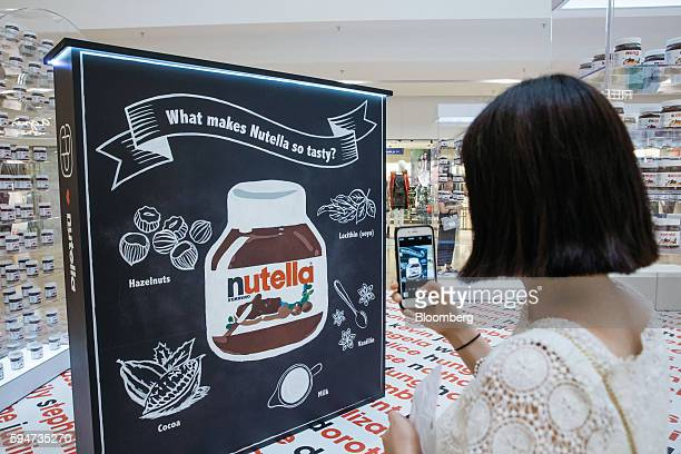 A woman takes a photograph using a smartphone at a Ferrero SpA's Nutella pop up store inside Pacific Place shopping mall in the Admiralty district of...
