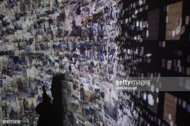A woman takes a photograph while viewing historical documents and photographs displayed in a high tech art installation at Salt Galata on May 6 2017...