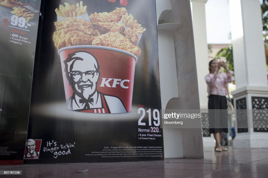 A woman takes a photograph with a smartphone near an advertisement for Yum! Brands Inc. KFC outside a restaurant in Bangkok, Thailand, on Saturday, Aug. 12, 2017. Thai Beverage, the spirits giant that makes Chang beer and SangSom rum, is expanding into the fast-food business to take advantage of the rising appetite for fried chicken in Asia. ThaiBev agreed to purchase more than 240 existing KFC restaurants in Thailand for about 11.3 billion Thai baht ($340 million). Photographer: Brent Lewin/Bloomberg via Getty Images