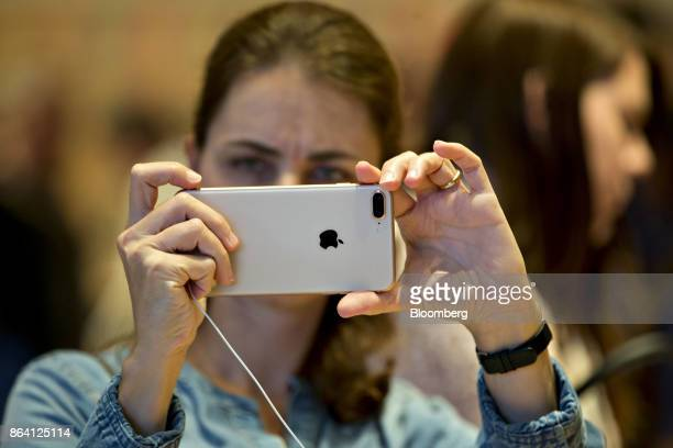 A woman takes a photograph with an iPhone 8 Plus during the opening of the new Apple Inc Michigan Avenue store in Chicago Illinois US on Friday Oct...