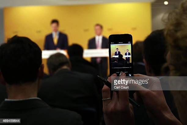 A woman takes a photograph with her phone during a press conference in which Liberal Democrat leader Nick Clegg and Chair of the Liberal Democrat...