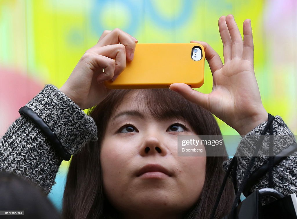 A woman takes a photograph with her smartphone in Tokyo, Japan, on Sunday, April 21, 2013. The number of smartphone subscribers in Japan surged to 37 percent of all contracts as of March 31 from 3 percent three years earlier, according to Tokyo-based MM Research Institute Ltd. Photographer: Yuriko Nakao/Bloomberg via Getty Images