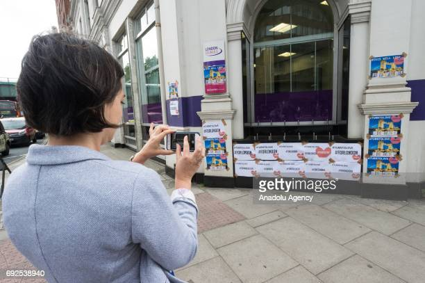 A woman takes a photos of posters with the hashtags #TURNTOLOVE and #FORLONDON on Southwark Street in London England on June 05 2017 This follows the...