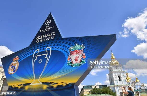 TOPSHOT A woman takes a picture as she walks past a star shaped billboard announcing the 2018 UEFA Champions League Final in the city centre of Kiev...