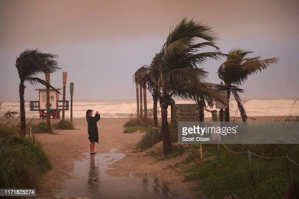 Woman takes a picture as the effects of Hurricane Dorian begin to be felt on September 2, 2019 in Cocoa Beach, Florida. Dorian, once expected to make...