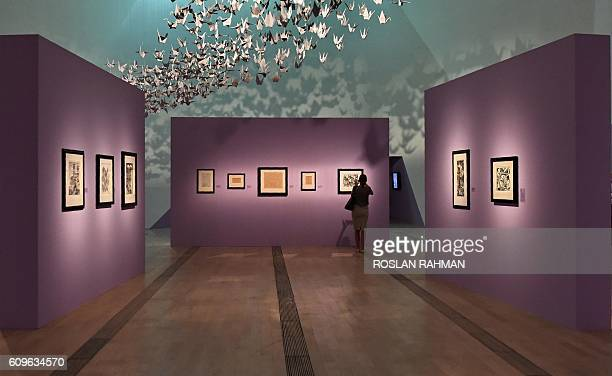 A woman takes a picture at the art exhibition 'Journey to Infinity Escher's World of Wonder' which showcases the works of world famous graphic...
