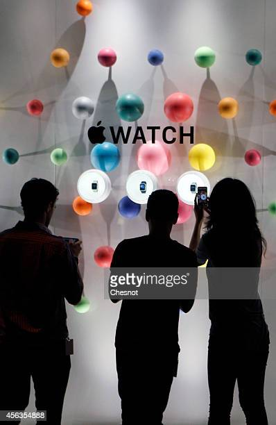 A woman takes a picture during the new Apple Watch display during an Apple special event at Colette store on September 30 2014 in Paris France Apple...