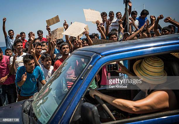 A woman takes a picture from her car of a group of Pakistani migrants who were protesting at their lack of progress obtaining transit papers on...