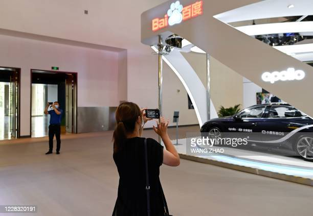 Woman takes a picture in front of a Baidu booth at the China National Convention Centre, the venue for the upcoming the China International Fair for...