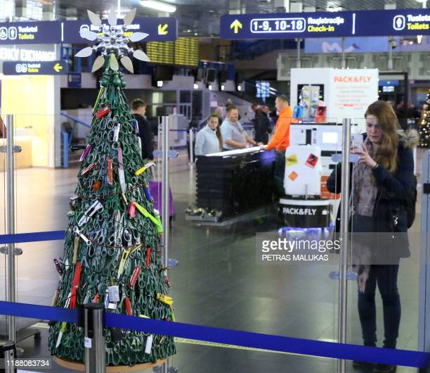 """Woman takes a picture of a """"Christmas tree"""" deftly made and decorated using items that passengers had to leave behind during screening displayed at..."""