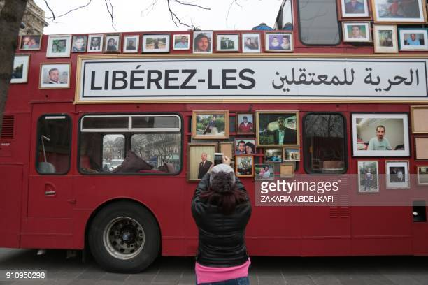 A woman takes a picture of a 'Freedom Bus' displaying portraits of people detained or missing after it was driven onto the Place de la Republique in...