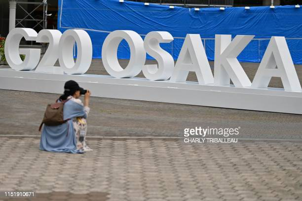 Woman takes a picture of a G20 Osaka design set up outside the venue for the G20 Osaka Summit in Osaka on June 26 ahead of the start of the summit...