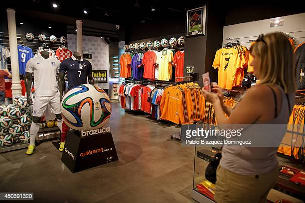 A woman takes a picture of a giant replica of the official match ball for the World Cup 'Brazuca' in a store on June 10 2014 in Madrid Spain Current...