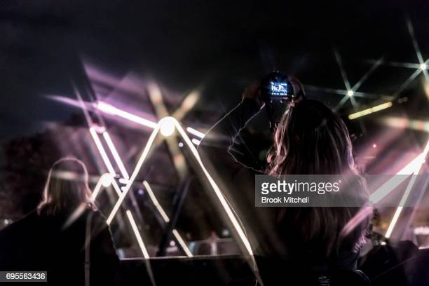A woman takes a picture of a light installation during the Vivid Festival on June 13 2017 in Sydney Australia Vivid Sydney is an annual festival that...