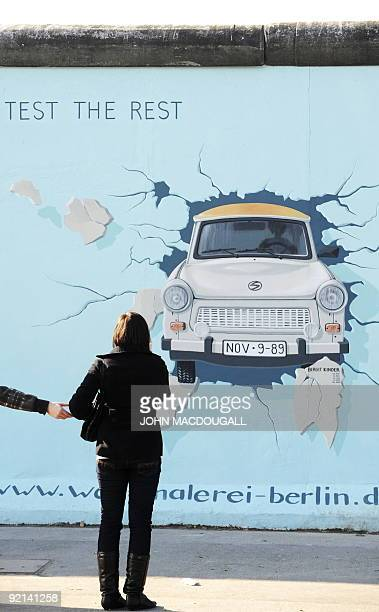A woman takes a picture of a painting on the so called East Side Gallery featuring an east German Trabant car smashing through the wall in Berlin...