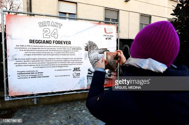 Woman takes a picture of a poster during the inauguration ceremony of a square named after late Los Angeles Lakers basketball star Kobe Bryant and...