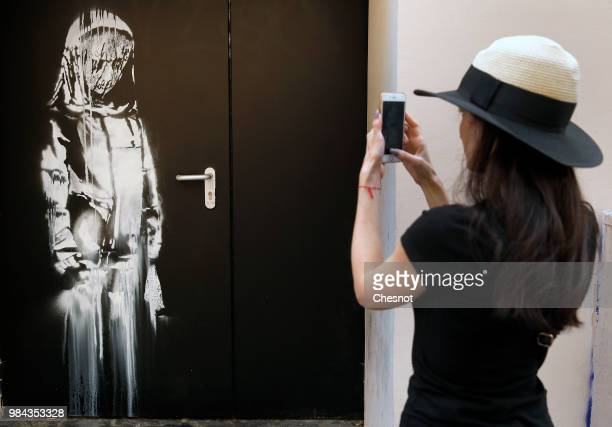 Woman takes a picture of a recent artwork attributed to street artist Banksy on June 26, 2018 in Paris, France. Yesterday a new artwork attributed to...