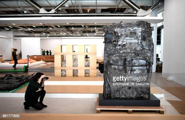 A woman takes a picture of a sculpture by French artist Cesar Baldaccini also known as Cesar to be displayed at the Centre Georges Pompidou art...