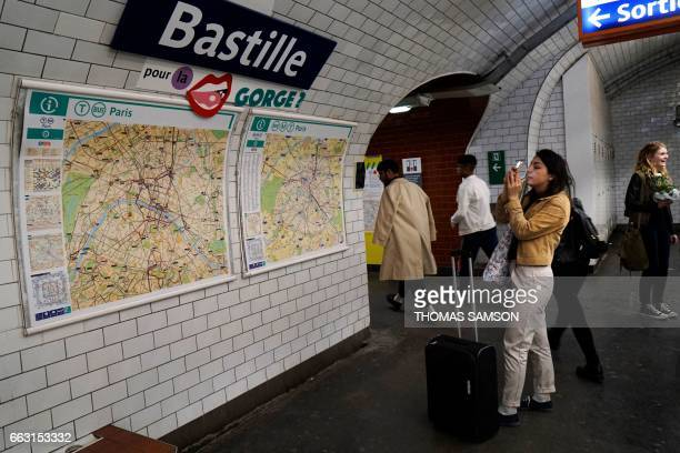 """Woman takes a picture of a sign of a play on words made with the sign of the Bastille metro station, reading """"a pill for the throat"""" in Paris, during..."""