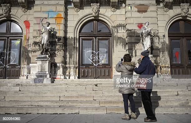 A woman takes a picture of a statue outside the Grand Theatre de Geneve opera house on December 20 2015 in Geneva after it was vandalised during a...