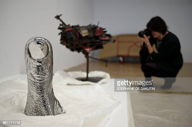 A woman takes a picture of a thumb sculpture by French artist Cesar Baldaccini also known as Cesar to be displayed at the Centre Georges Pompidou art...