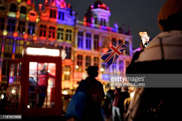 A woman takes a picture of a Union Jack flag during an event on Brussels' Grand Place to celebrate the friendship between Belgium and Britain in...