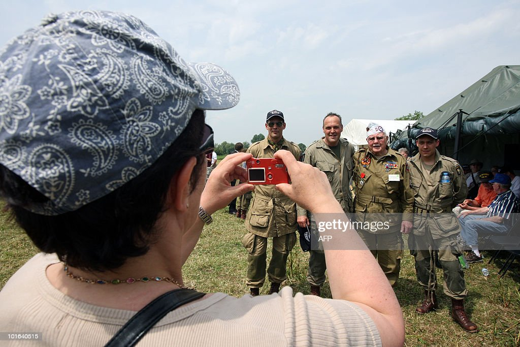 A woman takes a picture of a US veteran of the World War II (2ndR) on June 5, 2010 near Sainte-Mere-Eglise, during the D-Day celebrations to mark the 66th anniversary of the June 6, 1944 allied landings in France. AFP PHOTO KENZO