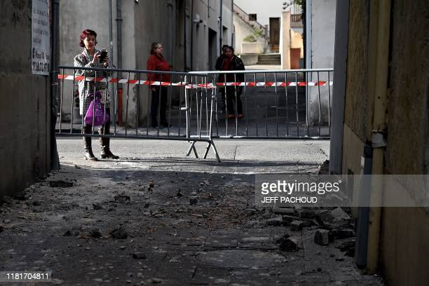 A woman takes a picture of bricks which fell from a wall in Le Teil southeastern France on November 11 after an earthquake with a magnitude of 54 hit...