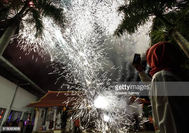 A woman takes a picture of fireworks in front of the Poo An Bio temple as a part of the Lunar New Year celebration in Lasem village of Rembang...