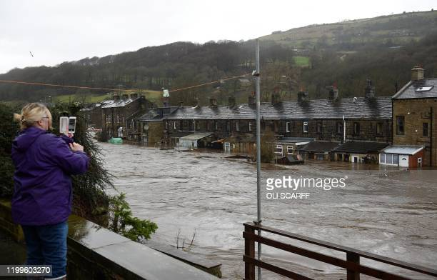 A woman takes a picture of flooded houses in Mytholmroyd northern England on February 9 after the River Calder burst its banks as Storm Ciara swept...