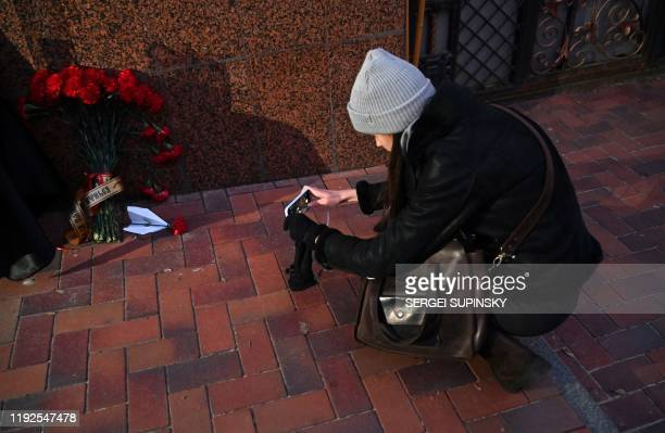 A woman takes a picture of flowers and paper airplane placed outside the Iranian embassy in Kiev on January 8 in remembrance of the victims of the...