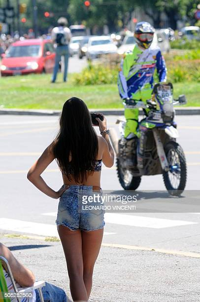 A woman takes a picture of French rider Florent Vayssade at the end of Stage 13 of the Rally Dakar 2016 between Villa Carlos Paz and Rosario...
