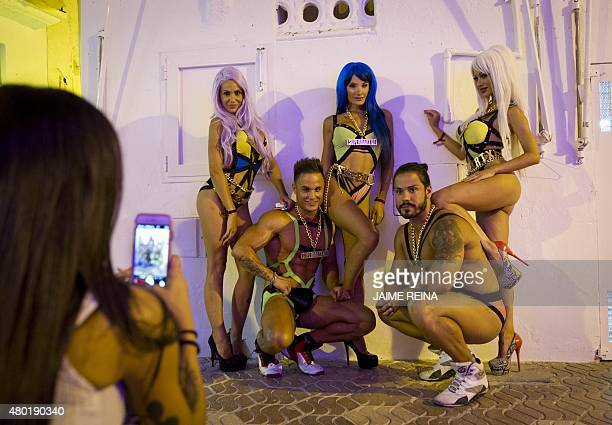 A woman takes a picture of gogo dancers promoting a disco in a tourist street in the city of Ibiza on July 9 2015 AFP PHOTO / JAIME REINA