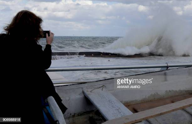 A woman takes a picture of high waves from Beirut's seafront promenade as heavy winds and rain whipped across Lebanon on January 19 2018 / AFP PHOTO...