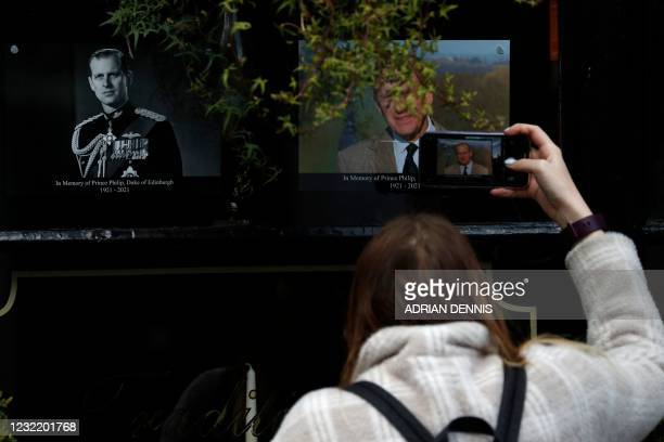 Woman takes a picture of portraits of Britain's Prince Philip, Duke of Edinburgh placed in the window of a pub in Windsor, west of London, on April 9...