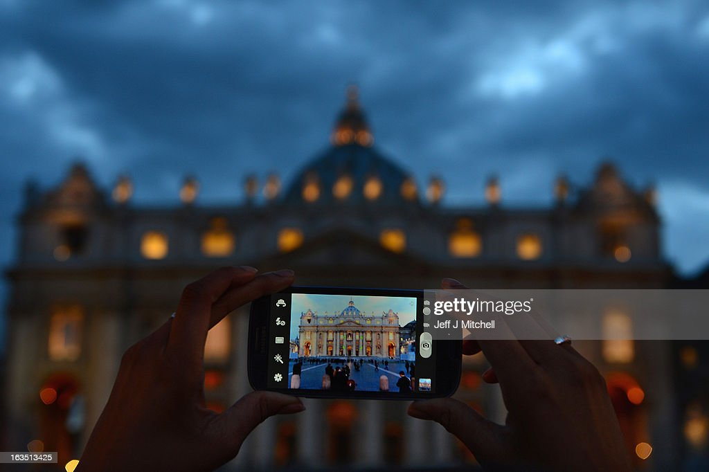 A woman takes a picture of St Peter's Basilica on March 11, 2013 in Vatican City, Vatican. Cardinals are set to enter the conclave to elect a successor to Pope Benedict XVI after he became the first pope in 600 years to resign from the role. The conclave is scheduled to start on March 12 inside the Sistine Chapel and will be attended by 115 cardinals as they vote to select the 266th Pope of the Catholic Church.