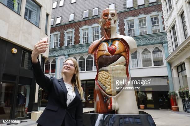 A woman takes a picture of 'Temple' a 2008 sculpture by British artist Damien Hirst in central London on June 24 2017 following its installation The...