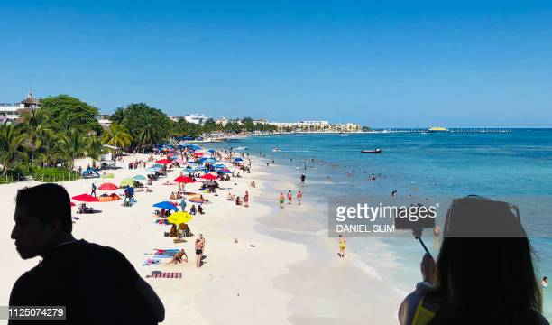 A woman takes a picture of the beach in the seaside tourist resort of Playa del Carmen Quintana Roo State on February 15 2019 Playa del Carmen and...