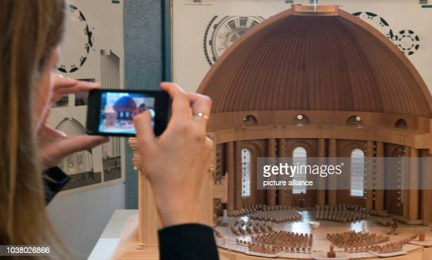 A woman takes a picture of the design for the redesign of the interior of St Hedwig's Cathedral by architect's office Sichau und Walter in Berlin...