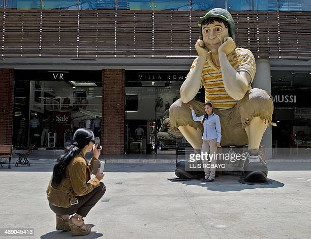A woman takes a picture of the sculpture of famou Latin American TV character El Chavo del Ocho starred by Mexican artist Roberto Gomez Bolaños aka...