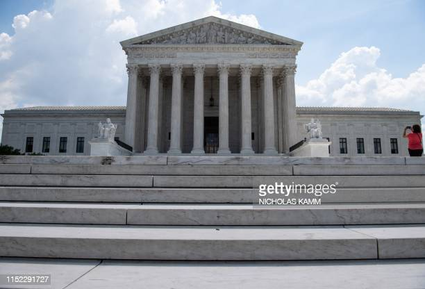 A woman takes a picture of the US Supreme Court in Washington DC on June 27 2019 The Supreme Court refused on June 27 to set limits on an ancient but...