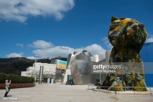 """Woman takes a picture of US artist Jeff Koons' installation """"Puppy"""" outside the usually overcrowded Guggenheim Bilbao Museum in the Spanish Basque..."""