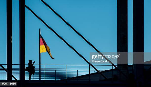 A woman takes a picture on a bridge in front of the german national flag on January 22 2016 in Berlin