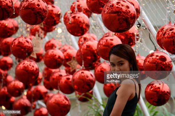 A woman takes a picture on display Christmas decorations to celebrate the upcoming Christmas season in front of a department store in Bangkok...