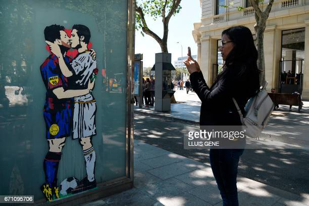 A woman takes a picture to the street art 'Love is blind' of Street artist Salva 'Tvboy' on April 21 2017 in Barcelona which shows Barcelona's...
